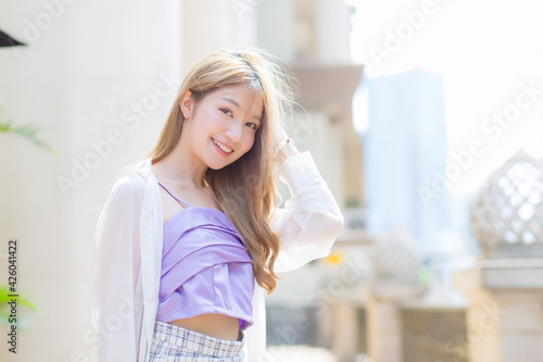 Fototapeta Asian beautiful girl with bronze long hair in purple camisole and white sleeve stands on the street as background on a sunny morning