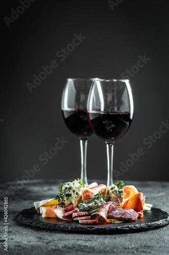 Obraz Italian antipasti wine snacks set. Cheese variety, janon, crudo, Prosciutto di Parma, salami and wine in glasses on dark background - fototapety do salonu