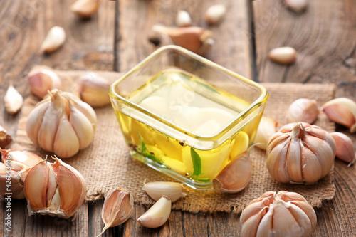Fototapeta Bowl of garlic oil on wooden background obraz