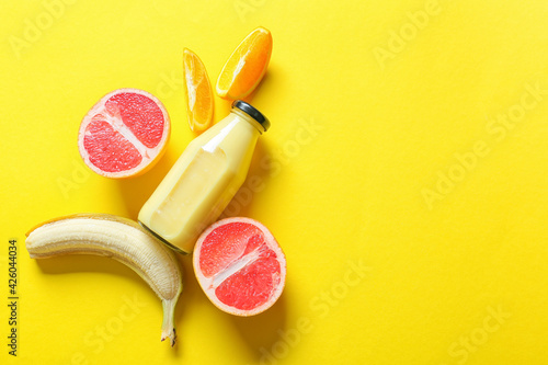Fotografija Bottle of tasty smoothie with fruits on color background