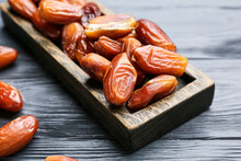 Board With Sweet Dried Dates On Color Wooden Background, Closeup