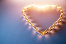 Golden Fish Oil Capsules Omega 3 Vitamins In Heart Shape On Purple Background