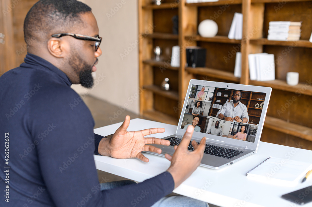 Fototapeta Virtual conference with employees, online briefing. Side view of a young African man in casual wear using laptop for video call, has video meeting with several people together. Remote work concept