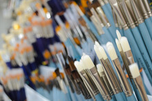 Close-up Of Different Brushes For Drawing Blue With White And Red Bristles. Selective Focus