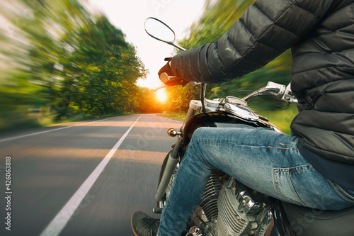 Fotografia The motorcyclist is riding through the empty asphalt road in the evening