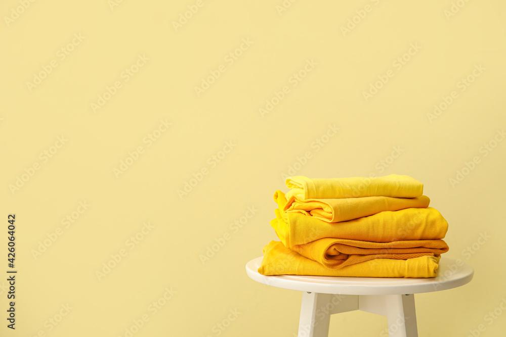Leinwandbild Motiv - Pixel-Shot : Table with stack of stylish clothes on color background
