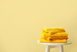 Table with stack of stylish clothes on color background