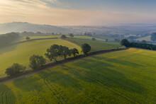 Aerial View Of Rolling Countryside At Dawn On A Hazy Summer Day, Devon, England, United Kingdom