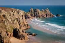 Treryn Dinas And Logan Rock Across The Beautiful Sandy Beach At Pedn Vounder, Cornwall, England, United Kingdom