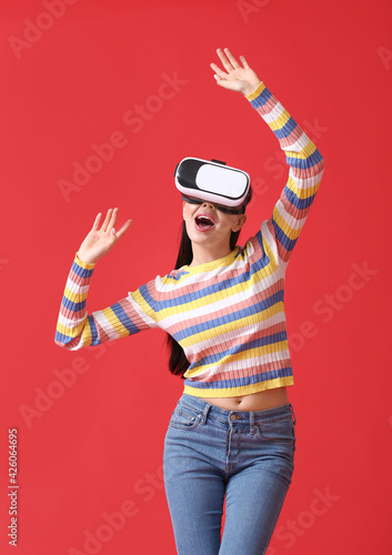 Obraz Young woman with VR glasses on color background - fototapety do salonu