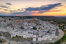 Aerial Panoramic Of White Buildings In The Old Town Of Ostuni At Sunset, Province Of Brindisi, Salento, Apulia, Italy