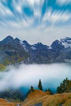Clouds In The Sky Above Lake Oeschinensee Covered By Fog, Bernese Oberland, Kandersteg, Canton Of Bern, Switzerland