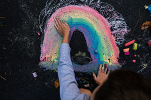 Young Boy Blending A Rainbow Art With His Hands And Chalk