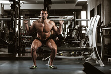 Fitness In Gym, Sport And Healthy Lifestyle Concept. Handsome Athletic Man With Naked Torso Making Exercises. Bodybuilder Male Model Training Muscles Making Squats With Barbell. Front View