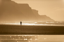 Person Walking Along Beach In The Evening Sunlight, Rhossili, Gower Peninsula, Swansea, Wales, United Kingdom