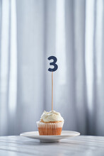 Anniversary Or Birthday Minimalistic Greeting Card Concept. Tasty Vanilla Cupcake Or Muffin With Number 3 Three On White Plate And Bright Background. High Quality Photo