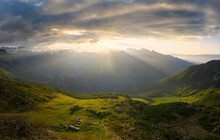 Sun Filters Between Clouds At Sunrise With Illuminated Pasture, Valmalenco, Valtellina, Lombardy, Italy