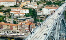 Top View On Iron Bridge And Pedestrians Walking Over Red Tile Roofs Of Historical Buildings. Porto.