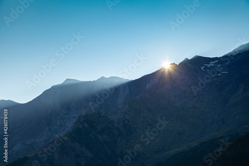 First light of dawn and the sun over the solitary mountains in summer, under a clean and huge blue sky, Aragonese Pyrenees, provincia de Huesca, Posets-Maladeta Natural Park.