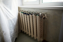 Old Heating Radiator With Peeling Paint Tied With A Cloth For Lying Cats