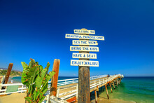 Malibu, California, United States - August 7, 2018: Paradise Cove Pier Sign And Wooden Jetty In Paradise Cove Beach, Malibu. Summer Blue Sky, Copy Space. Luxurious Travel Destination On Pacific Coast.