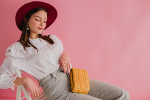 Fashionable Brunette Girl Wearing Stylish White Vintage Cotton Shirt With Lace Collar, Marsala Color Hat, Jeans, With Yellow Padded Leather Bag, Posing On Pink Background. Copy, Empty Space For Text