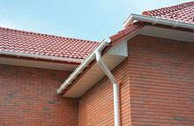 A Close-up On Plastic Rain Gutters, Downspout, Soffit And Fascia With A Box-end On The Corner Of A Brick House As Important Parts Of Roofing System Waterproofing And Ventilation.