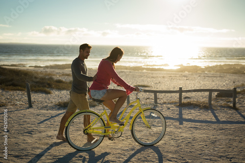Happy caucasian couple at the sea learning to ride bicycle