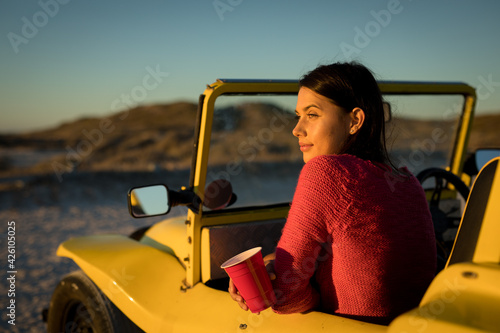 Happy caucasian woman sitting in beach buggy by the sea holding red cup