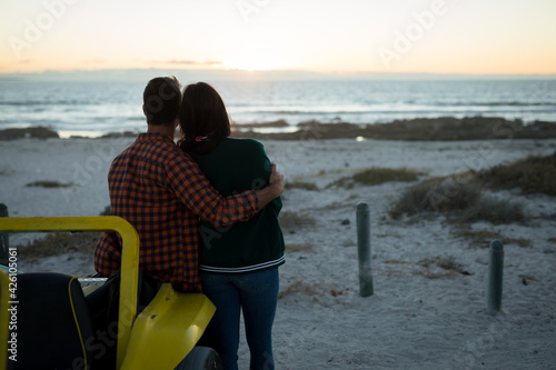Happy caucasian couple leaning against beach buggy by the sea during sunset embracing