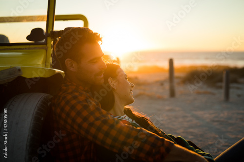 Happy caucasian couple leaning against beach buggy by the sea relaxing during sunset