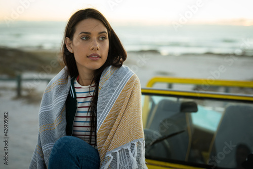 Happy caucasian woman sitting on beach buggy by the sea wearing shawl looking ahead