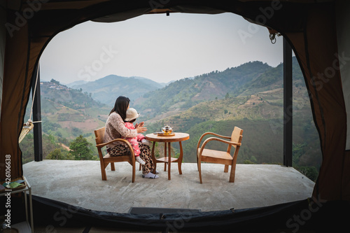 Fototapeta mother and daughter sitting on the wood table and drinking hot green tea at moun