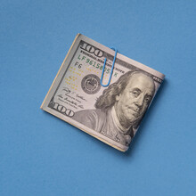 Folded One Hundred Dollar Bill With Paper Clip On Blue Background