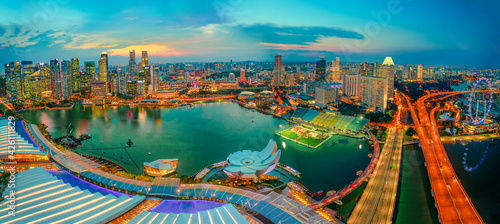 Fototapeta Singapore - May, 2018: Wide panorama at sunset and blue hour of Singapore Marina Bay with illuminated skyscrapers of the financial district in the downtown of the city. Singapore cityscape aerial view obraz