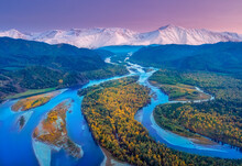 Autumn View Of The River Bed With Shallows Of Yellow Trees After Sunset Against The Background Of High Mountains, The Abakan River In Khakassia
