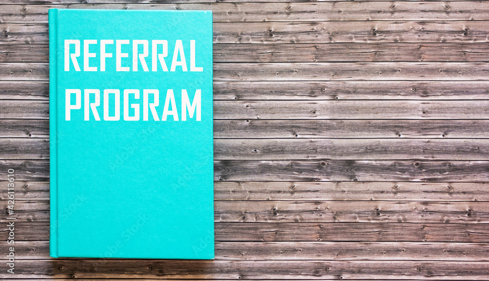 Fototapeta Notepad with tekst Referral program, business concept on wooden table.