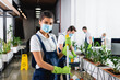 canvas print picture African american cleaner in medical mask holding mop while colleagues working on blurred background in office
