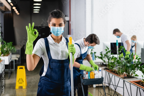 Fototapeta African american worker of cleaning company in medical mask holding mop and showing ok gesture in office obraz
