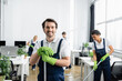 canvas print picture Cleaner with mop smiling at camera near african american colleague in office on blurred background
