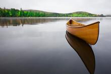 United States, New York, Saranac Lake, Wooden Canoe Floating On Calm Upper Saranac Lake