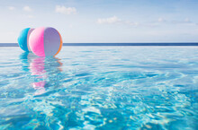 Beach Balls Floating On Water In Infinity Pool