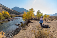 United States, Idaho, Sun Valley, Senior Woman Looking Through Binoculars While Standing By River In Autumn Landscape