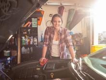 Woman Fixing Car In Garage