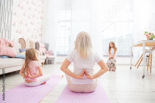 Fotografia Smiling blond mother on yoga mat with cute playful daughter do exercises