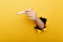 A Hand With Marker Though A Broken Yellow Paper Wall.