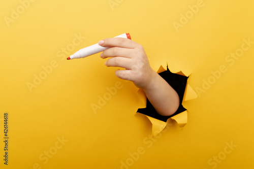 Obraz A hand with marker though a broken yellow paper wall. - fototapety do salonu