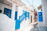 Fototapeta Uliczki - The narrow streets of the island with blue balconies, stairs and flowers in Greece.