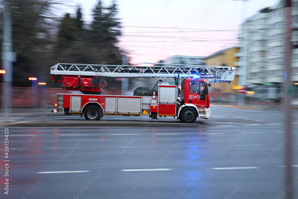 Samochód straży pożarnej z drabiną alarmowo na sygnale.  - obrazy, fototapety, plakaty