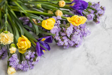 Yellow Narcissus Flowers And Purple Irises In A Line Floral Arrangement Isolated On Marble Background. Flowers Composition.Spring, 8 Of March, Woman Day, Mothers Day, Easter Concept. Copy Space.